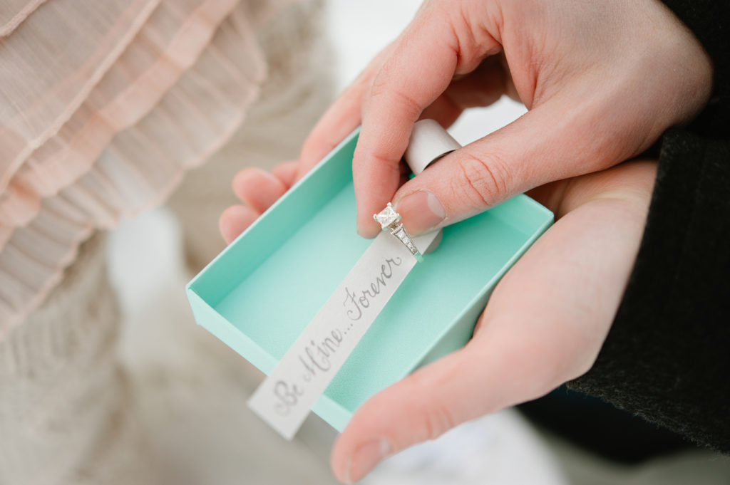 wedding proposal with ring in a Tiffany box